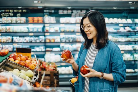 young asian woman shopping for fresh organic fruits royalty free image 973060642 1560416617
